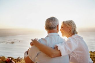 A loving senior couple looking into one another's eyes against a beautiful sunset - Copyspace